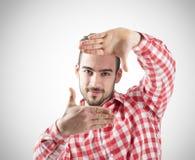 Νέο γενειοφόρο άτομο που παρουσιάζει πλαίσιο δάχτυλων που εξετάζει τη κάμερα Στοκ Φωτογραφία