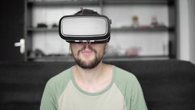 Νέο γενειοφόρο άτομο hipster που χρησιμοποιεί την επίδειξη κασκών VR του για την προσοχή του βίντεο 360 καθμένος στον καναπέ και  απόθεμα βίντεο