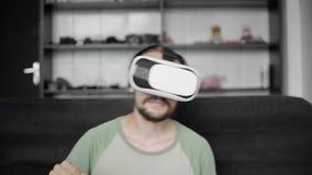 Νέο γενειοφόρο άτομο hipster που χρησιμοποιεί την επίδειξη κασκών VR του για την προσοχή των 360 τηλεοπτικών και των αισθήσεων δε φιλμ μικρού μήκους