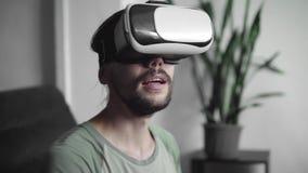 Νέο γενειοφόρο άτομο hipster χρησιμοποιώντας την επίδειξη κασκών VR του για το παιχνίδι εικονικής πραγματικότητας ή προσέχοντας τ απόθεμα βίντεο