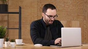 Νέο γενειοφόρο καφές ή τσάι κατανάλωσης ατόμων εργαζόμενων στο lap-top απόθεμα βίντεο