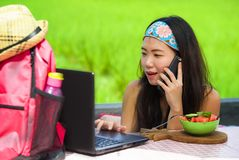 Νέο γλυκό και αρκετά ασιατικό κινεζικό κορίτσι backpacker που εργάζεται on-line με την ομιλία φορητών προσωπικών υπολογιστών ευτυ στοκ φωτογραφία