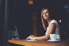 Νέο γοητευτικό θηλυκό freelancer που σκέφτεται για τις νέες ιδέες κατά τη διάρκεια της εργασίας για το φορητό προσωπικό υπολογιστ Στοκ φωτογραφία με δικαίωμα ελεύθερης χρήσης