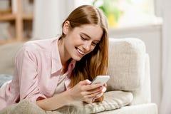 Νέο γοητευτικό κορίτσι, στον καναπέ, γράψιμο χαμόγελου sms στο τηλέφωνο κυττάρων Στοκ φωτογραφίες με δικαίωμα ελεύθερης χρήσης