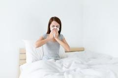 Νέο γυναικείο sneeze στο κρεβάτι και χρειάζεται περισσότερο υπόλοιπο στοκ φωτογραφία με δικαίωμα ελεύθερης χρήσης