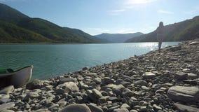 Νέο γυναικών εμπρός το ηλιοφώτιστο riverbank στα βουνά την ηλιόλουστη ημέρα απόθεμα βίντεο