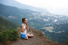 Νέο γυναικών υπαίθρια, κορίτσι που κάνει τη γιόγκα υψηλή στα βουνά, έννοια μόνος-αντανάκλασης χαλάρωσης Στοκ φωτογραφία με δικαίωμα ελεύθερης χρήσης