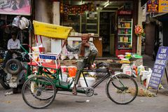 Νέο Δελχί, Ινδία στις 10 Απριλίου 2016: Μη αναγνωρισμένο άτομο που καπνίζει με τη δίτροχο χειράμαξά του που περιμένει τους ανθρώπ Στοκ εικόνα με δικαίωμα ελεύθερης χρήσης
