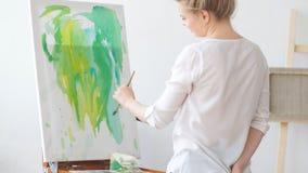 Νέο δημιουργικό κορίτσι που έχει τη διασκέδαση με το χρώμα και τη βούρτσα απόθεμα βίντεο
