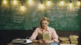 Νέο διαβασμένο βιβλίο γυναικών σπουδαστών μπροστά από τον πίνακα κιμωλίας Πορτρέτο του νέου βιβλίου ανάγνωσης δασκάλων από τον πί απόθεμα βίντεο