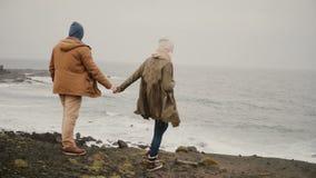 Νέο διακινούμενο ζεύγος που περπατά στην ακτή της θάλασσας Ελκυστικό φίλημα ανδρών και γυναικών κοντά στο νερό απόθεμα βίντεο