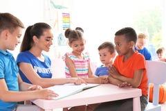 Νέο εθελοντικό βιβλίο ανάγνωσης με τα παιδιά στον πίνακα στοκ εικόνα με δικαίωμα ελεύθερης χρήσης