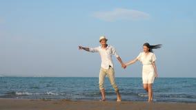 Νέο ειδύλλιο απόλαυσης ζευγών ερωτευμένο στον κομψό ιματισμό στην παραλία σε αργή κίνηση φιλμ μικρού μήκους