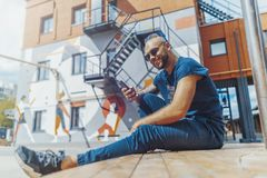 Νέο ελκυστικό άτομο με τα μπλε dreadlocks που εξετάζει την κινητή τηλεφωνική οθόνη στοκ φωτογραφία