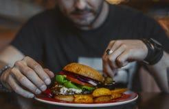 Νέο ελκυστικό άτομο που τρώει burger και τις τηγανιτές πατάτες στον καφέ στοκ φωτογραφία με δικαίωμα ελεύθερης χρήσης