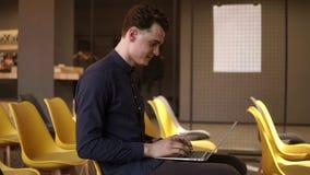 Νέο ελκυστικό αρσενικό που δακτυλογραφεί κάτι σε ένα lap-top Διαδικασία εργασίας Νεολαία, εκπαίδευση απόθεμα βίντεο