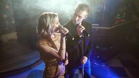 Νέο ελκυστικό ζεύγος που εκτελεί ένα τραγούδι σε ένα σκοτεινό καπνώές δωμάτιο απόθεμα βίντεο