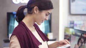 Νέο ελκυστικό θηλυκό κοστούμι που χαμογελά εξετάζοντας και κρατώντας ένα pricetag στο κατάστημα συσκευών Τμήμα φιλμ μικρού μήκους