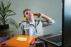 Νέο ελκυστικό και ευτυχές άτομο με τα κίτρινα ακουστικά που κάθεται στο σπίτι το γραφείο γραφείων που λειτουργεί με το φορητό προ Στοκ εικόνα με δικαίωμα ελεύθερης χρήσης