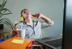 Νέο ελκυστικό και ευτυχές άτομο με τα κίτρινα ακουστικά που κάθεται στο σπίτι το γραφείο γραφείων που λειτουργεί με το φορητό προ Στοκ φωτογραφίες με δικαίωμα ελεύθερης χρήσης