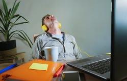 Νέο ελκυστικό και ευτυχές άτομο με τα κίτρινα ακουστικά που κάθεται στο σπίτι το γραφείο γραφείων που λειτουργεί με το φορητό προ Στοκ Εικόνες
