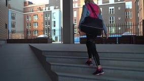 Νέο, ελκυστικό και φίλαθλο ξανθό περπάτημα κοριτσιών υπαίθριο με μια αθλητική τσάντα Υγειονομική περίθαλψη, ικανότητα και τρόπος  φιλμ μικρού μήκους
