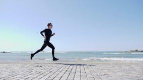 Νέο ελκυστικό κατάλληλο καυκάσιο άτομο στο μαύρο τρέξιμο σε μια αποβάθρα γρήγορα σε αργή κίνηση απόθεμα βίντεο