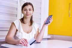 Νέο ελκυστικό κορίτσι με το smartphone και την πλαστική πιστωτική κάρτα υπό εξέταση Σε απευθείας σύνδεση πληρωμές στο σε απευθεία στοκ εικόνα