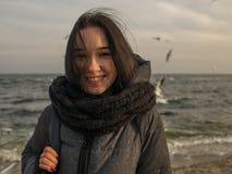 Νέο ελκυστικό κορίτσι πορτρέτων στο υπόβαθρο της θάλασσας, του ουρανού και των γλάρων στοκ εικόνα με δικαίωμα ελεύθερης χρήσης