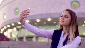 Νέο ελκυστικό κορίτσι που παίρνει ένα selfie σε ένα smartphone το βράδυ, στο κέντρο πόλεων φιλμ μικρού μήκους