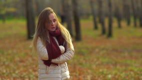 Νέο ελκυστικό κορίτσι που παγώνει στο πάρκο φθινοπώρου, θερμά χέρια φιλμ μικρού μήκους