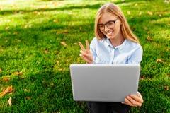 Νέο ελκυστικό κορίτσι στα γυαλιά, καθμένος με ένα lap-top, μιλώντας σε Skype και παρουσιάζοντας δύο δάχτυλα, σε μια οθόνη lap-top στοκ φωτογραφίες