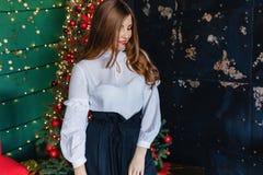 Νέο ελκυστικό κορίτσι στον εορταστικό ιματισμό στο υπόβαθρο ενός χριστουγεννιάτικου δέντρου, νέα έννοια έτους στοκ εικόνα με δικαίωμα ελεύθερης χρήσης