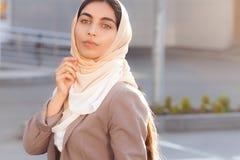 Νέο ελκυστικό κορίτσι στο επιχειρησιακό κοστούμι και hijab στην οδό στοκ εικόνα