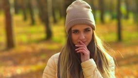 Νέο ελκυστικό κορίτσι στο πάρκο φθινοπώρου εξετάζει τη κάμερα και τα χαμόγελα, παρουσιάζουν διαφορετικές συγκινήσεις, αγγίζουν το απόθεμα βίντεο