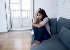 Νέο ελκυστικό λατινικό ανησυχημένο καναπές sufferi γυναικών στο σπίτι Στοκ Φωτογραφία