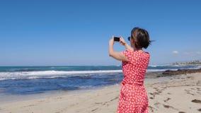 Νέο ελκυστικό τηλέφωνο καμερών εκμετάλλευσης γυναικών και λήψη των εικόνων των κυμάτων θάλασσας θύελλας που στέκονται στην παραλί φιλμ μικρού μήκους