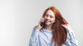 Νέο ελκυστικό Redhead κορίτσι που μιλά τηλεφωνικώς με το φίλο και το χαμόγελο απόθεμα βίντεο