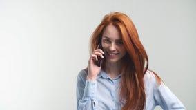 Νέο ελκυστικό Redhead κορίτσι που μιλά τηλεφωνικώς με το φίλο και το χαμόγελο φιλμ μικρού μήκους