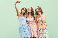 Νέο ενήλικο πρότυπο, που selfie, κοίταγμα στην έξυπνη τηλεφωνική οθόνη και χαμόγελο Απομονωμένος στην πράσινη ανασκόπηση Στοκ Εικόνες