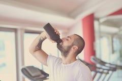 Νέο ενήλικο μπουκάλι νερό κατανάλωσης ατόμων στο trreadmill στη γυμναστική στοκ φωτογραφίες με δικαίωμα ελεύθερης χρήσης