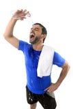 Νέο εξαντλημένο άτομο χύνοντας νερό ελκυστικού και αθλητικού αθλητισμού στο πρόσωπό του Στοκ εικόνες με δικαίωμα ελεύθερης χρήσης