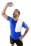 Νέο εξαντλημένο άτομο χύνοντας νερό ελκυστικού και αθλητικού αθλητισμού στο πρόσωπό του Στοκ Εικόνα