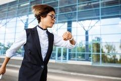 Νέο επιτυχές τρέξιμο επιχειρηματιών, που εξετάζει το ρολόι πέρα από το επιχειρησιακό κέντρο Στοκ Εικόνες