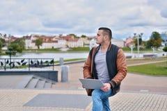Νέο επιτυχές freelancer στο σακάκι δέρματος που λειτουργεί στο stree στοκ φωτογραφίες