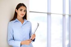 Νέο επιχειρηματίας brunette ή κορίτσι σπουδαστών που εξετάζει τη κάμερα Στοκ Εικόνα