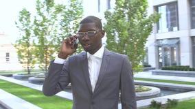 Νέο επιχειρησιακό άτομο αφροαμερικάνων που χρησιμοποιεί ένα κινητό τηλέφωνο - μαύροι απόθεμα βίντεο