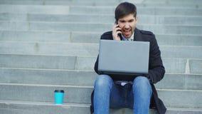 Νέο επιχειρησιακό άτομο με το φορητό προσωπικό υπολογιστή που έχει την πίεση μετά από το τηλεφώνημα και που κάθεται στα σκαλοπάτι στοκ φωτογραφία