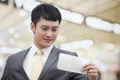 Νέο επιχειρησιακό άτομο που εξετάζει το εισιτήριο πτήσης Στοκ Φωτογραφία