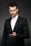 Νέο επιχειρησιακό άτομο που εξετάζει το τηλέφωνο Στοκ φωτογραφία με δικαίωμα ελεύθερης χρήσης